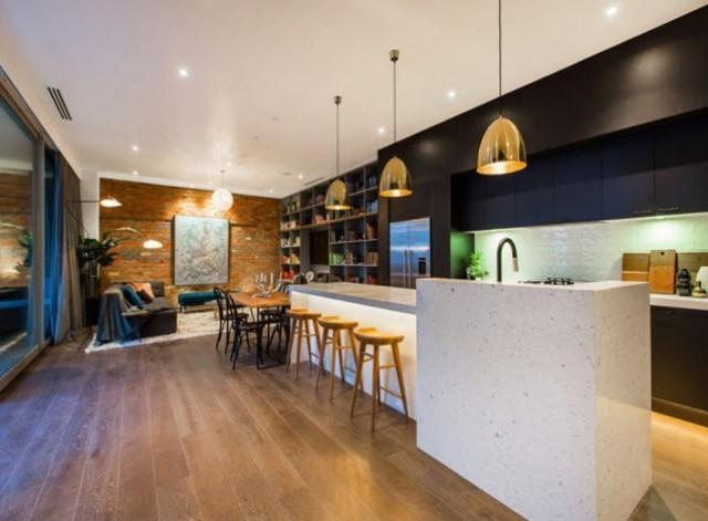 黑色的顶天壁柜,大理石台面的中岛,上方的金色吊灯,让开放式厨房